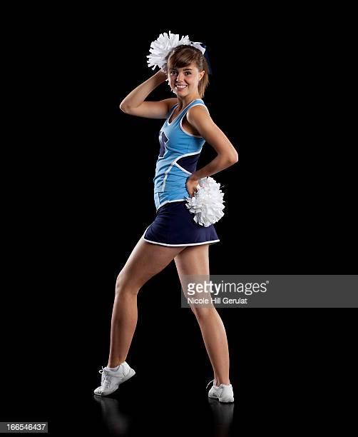 studio shot of cheerleader (16-17) striking pose - short skirt teens stock photos and pictures