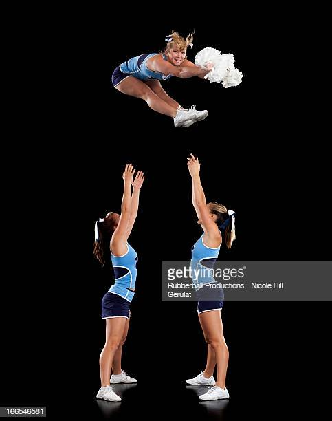 studio shot of cheerleaders (16-17) assisting friend during jump - cheerleader up skirt stock photos and pictures