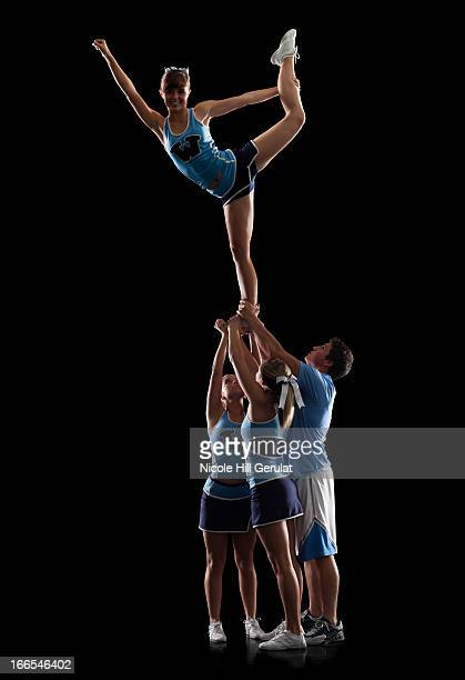 Studio shot of cheerleaders (16-17) supporting friend standing on one leg