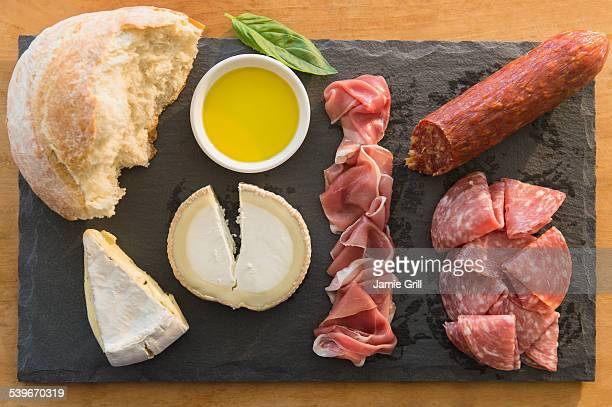 Studio shot of cheese, meat and bread on pate