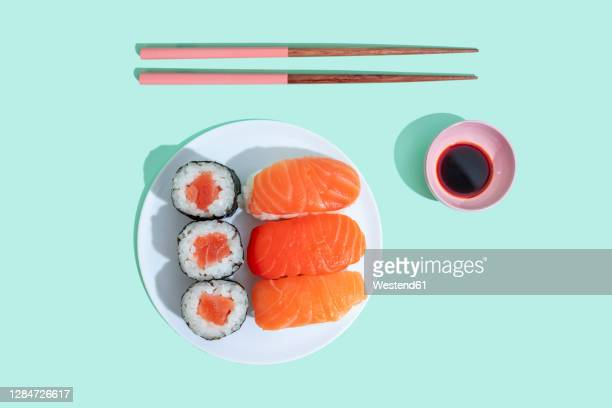 studio shot of chopsticks, bowl of soy sauce and plate of maki sushi and nigiri - maki sushi stock pictures, royalty-free photos & images