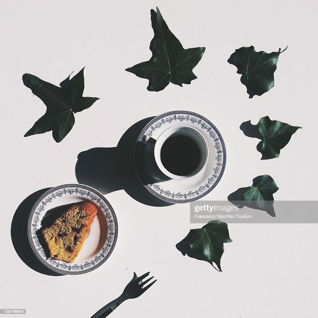 Studio Shot Of Coffee Cup And Cake Surrounded By Ivy Leaves : Foto stock