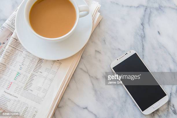 Studio shot of coffee cup, newspaper and smart phone
