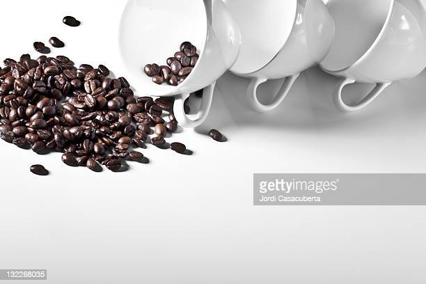 Studio shot of coffee cups and spilling coffee beans