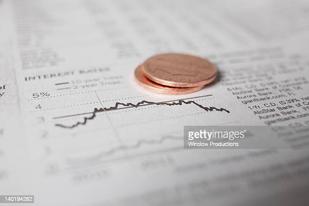 studio shot of coins on financial newspaper - interest rate stock pictures, royalty-free photos & images