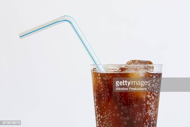 studio shot of cold drink with ice cubes and plastic straw on white background - koude dranken stockfoto's en -beelden