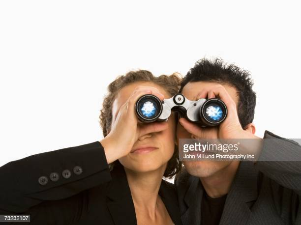 Studio shot of couple looking through binoculars
