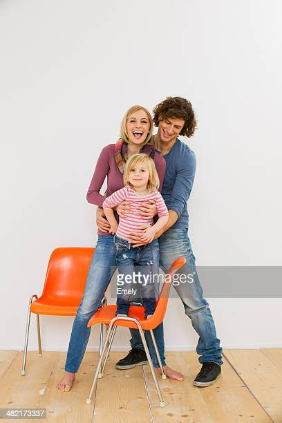Studio shot of couple with young daughter standing on chair