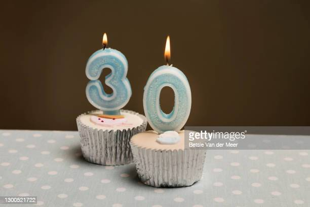 studio shot of cupcakes with burning candles on top with the numbers 30. - candle stock pictures, royalty-free photos & images