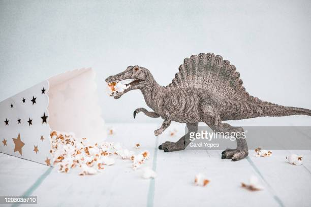 studio shot of dinosaur toy eating pop corns - sauropoda stock pictures, royalty-free photos & images