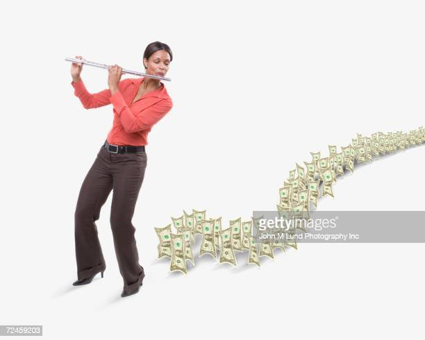 studio shot of dollar bills following woman playing flute - american influenced stock photos and pictures