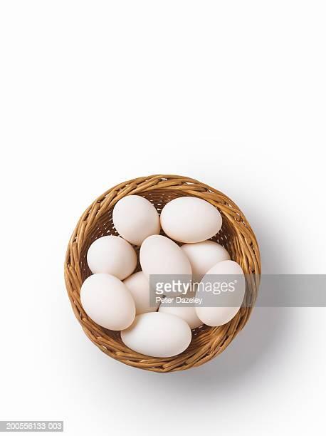 Studio shot of eggs in woven basket, overhead view