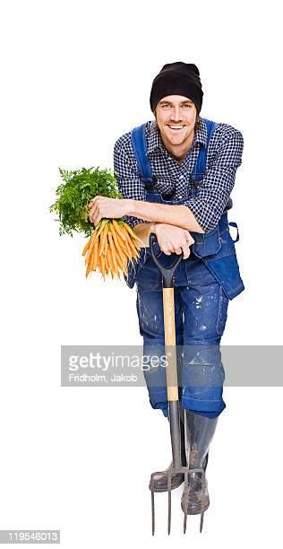 Studio shot of farmer holding carrots