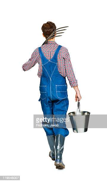 Studio shot of farmer with pitchfork and bucket