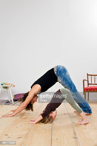 Studio shot of father and daughter bending over on floor