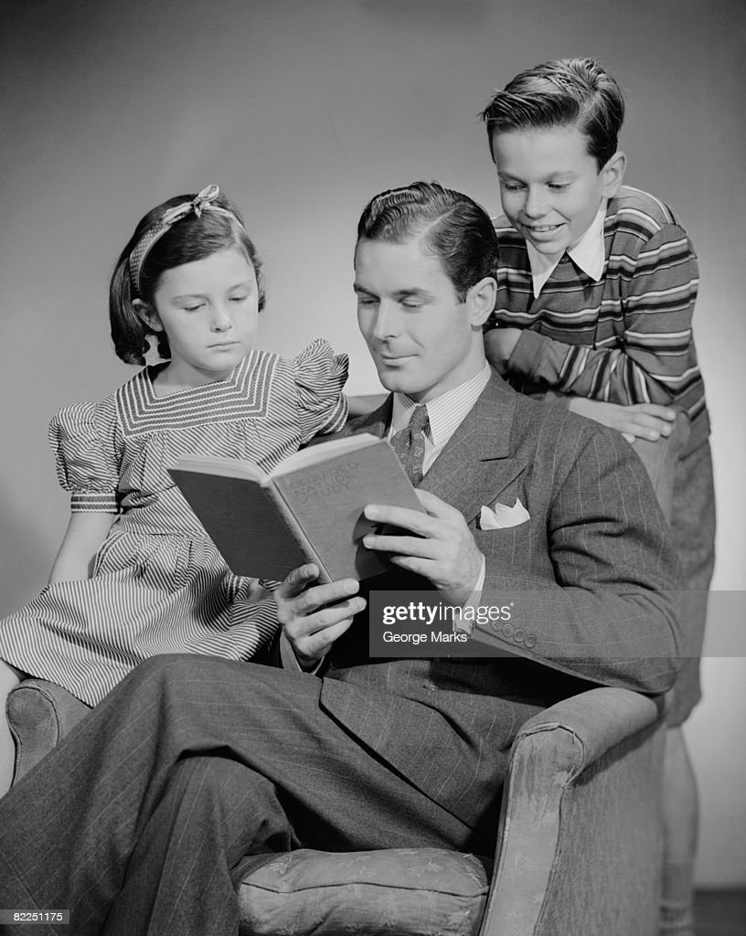 Studio shot of father with two children (10-11) reading book : Stock Photo