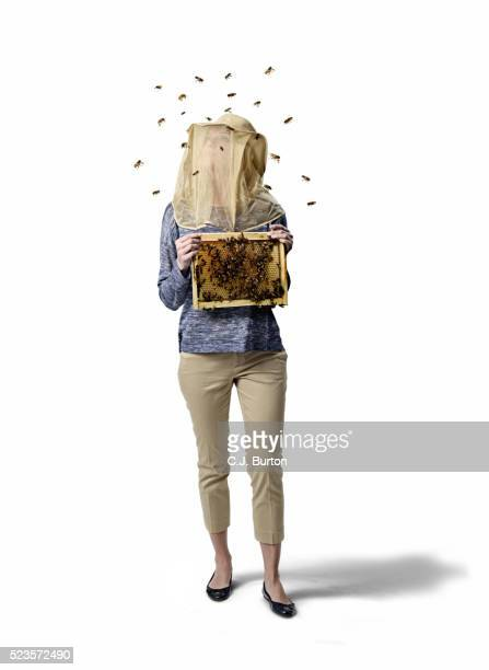 Studio shot of female beekeeper with obscured face, white background