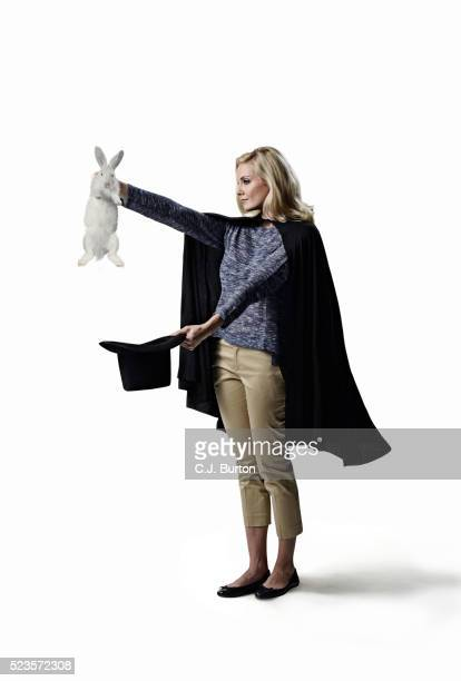 Studio shot of female magician with hat and rabbit