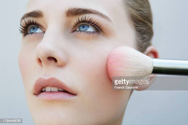 studio shot of female model and pink blusher brush - beautiful women stock pictures, royalty-free photos & images