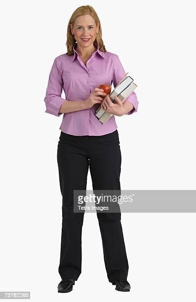 Studio shot of female teacher holding books
