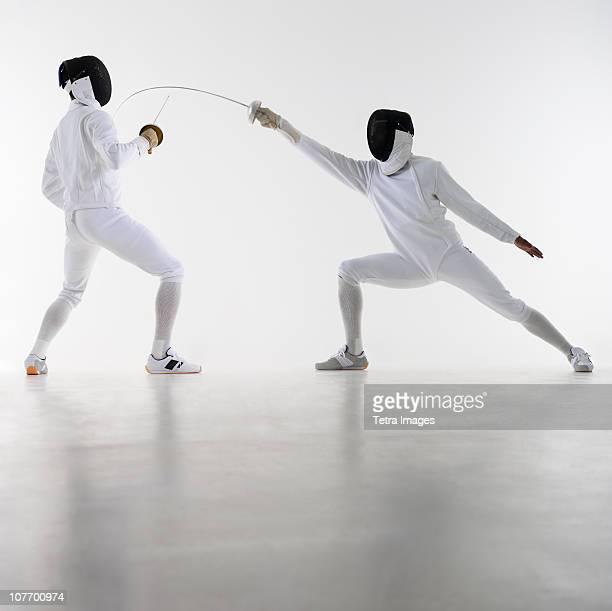 studio shot of fencers in attacking lunge - esgrima esporte de combate - fotografias e filmes do acervo