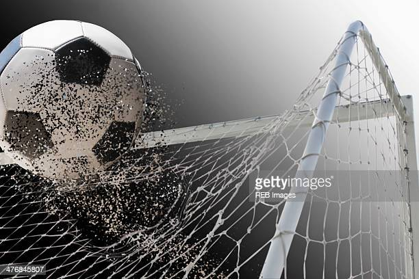 Studio shot of football powering through goal netting