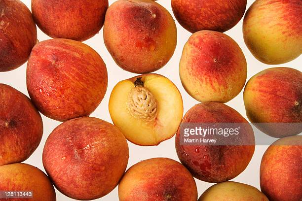 Studio shot of fresh halved peach with pit among whole peaches