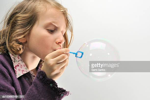 Studio shot of girl (6-7) blowing bubbles