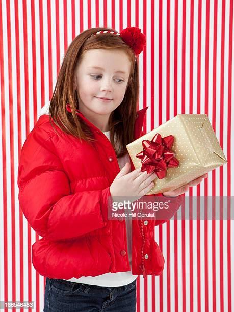 Studio shot of girl (4-5) holding of Christmas gift