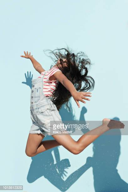 studio shot of girl jumping in sunlight on studio backdrop - throwing stock pictures, royalty-free photos & images