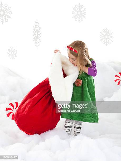 Studio shot of girl (18-23 months) peeking to Santa bag
