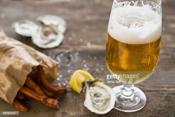 Studio shot of glass of beer, oysters and french fries