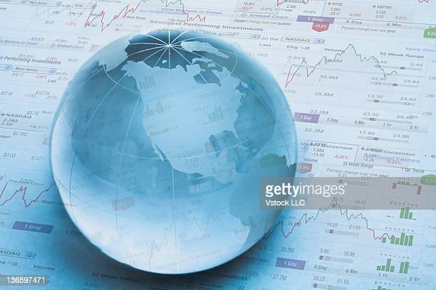Studio shot of globe on financial pages