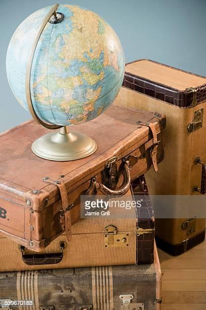 Studio shot of globe on suitcases