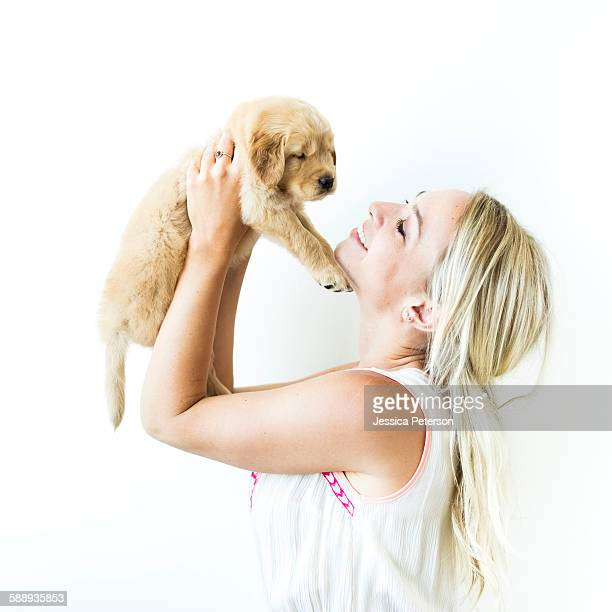 Studio shot of Golden Retriever puppy with owner