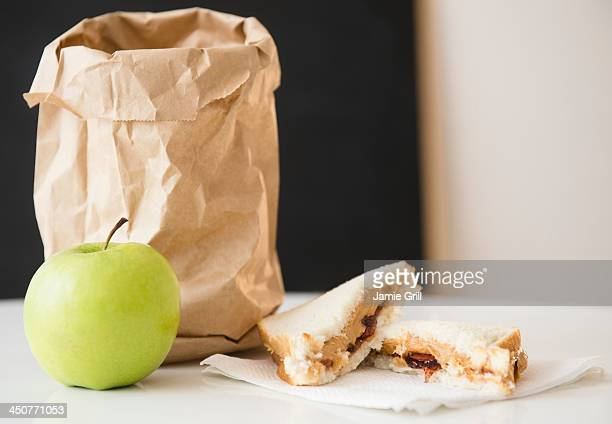 Studio Shot of green apple and sandwich next to paper bag