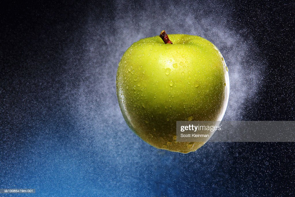 Studio shot of green apple with drops and spray : Foto stock