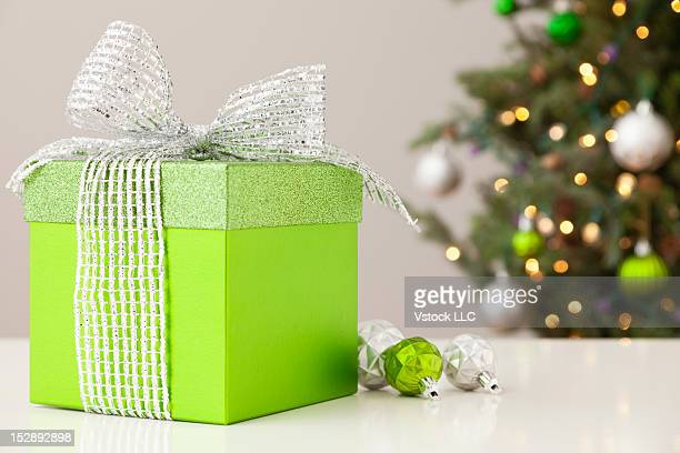 Studio shot of green gift on table with christmas tree in background