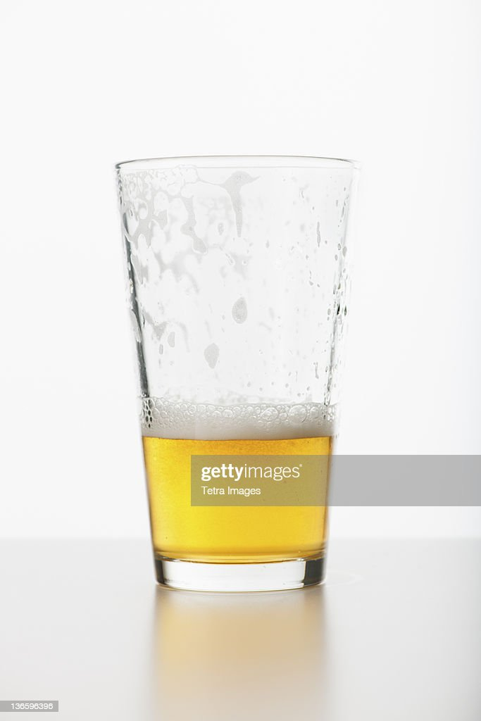 Studio shot of half full beer glass : Stock Photo