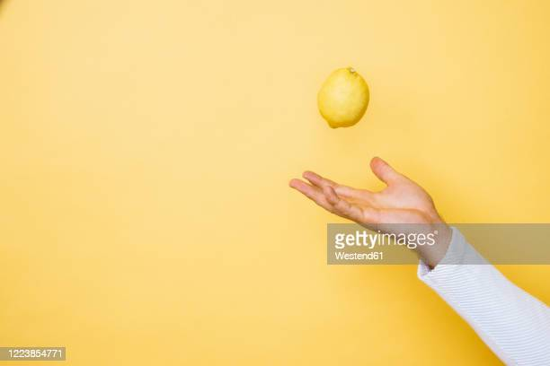 studio shot of hand of person tossing up lemon - arremessar imagens e fotografias de stock