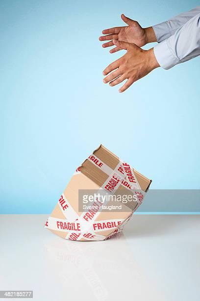Studio shot of hands dropping cardboard box marked fragile
