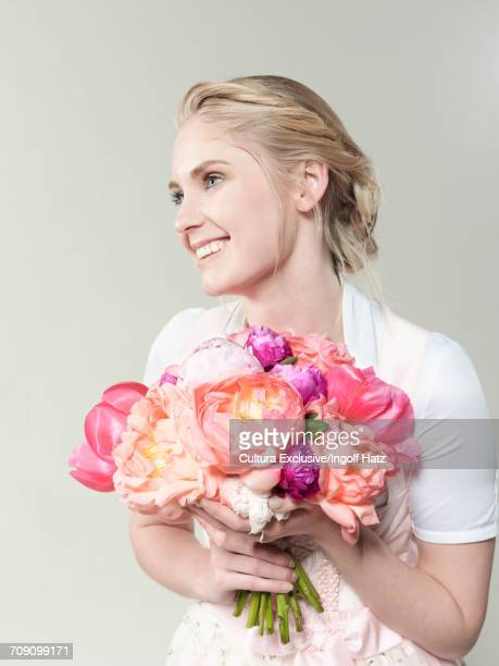 Studio shot of happy young bride holding rose bouquet