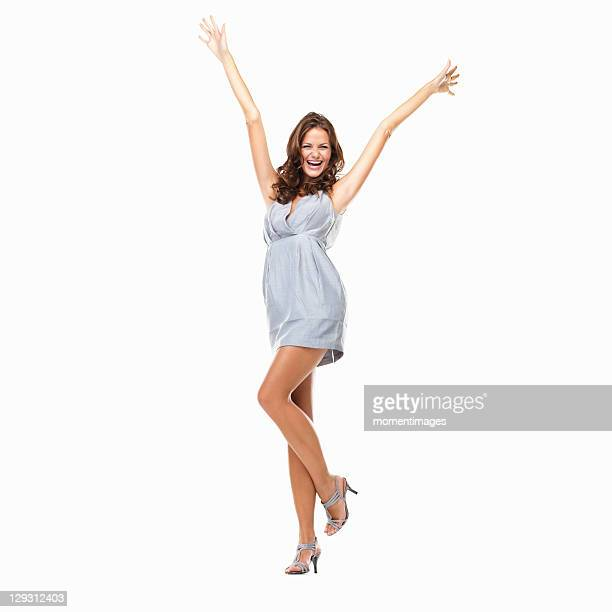 Studio shot of happy young woman celebrating with hands raised