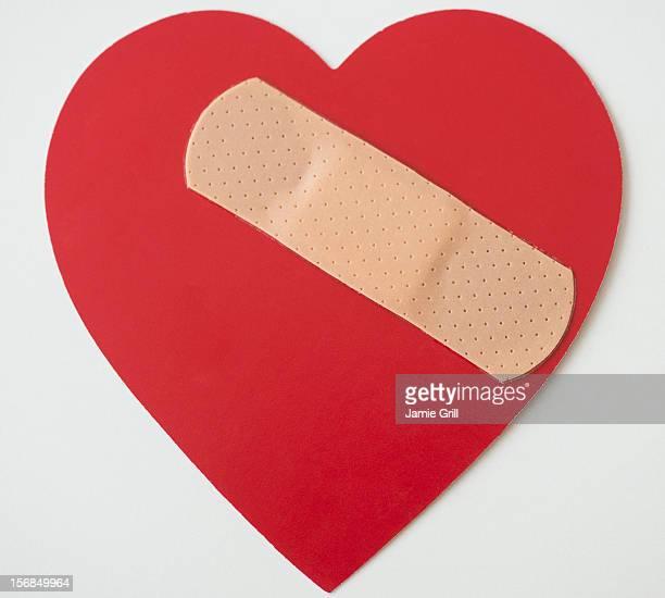 Studio shot of heart with adhesive bandage