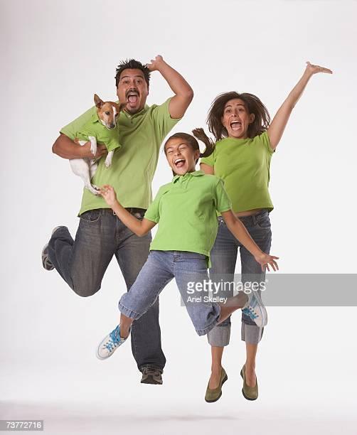 Studio shot of Hispanic family jumping