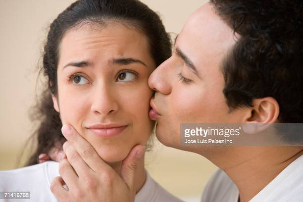 Studio shot of Hispanic man kissing Hispanic woman's cheek