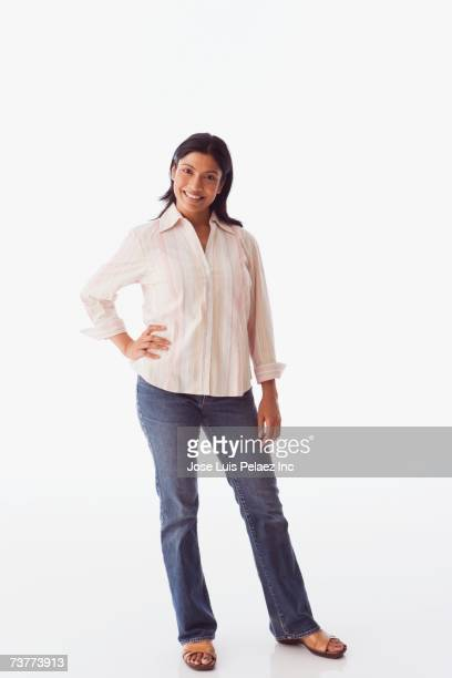Studio shot of Indian woman standing with hand on hip