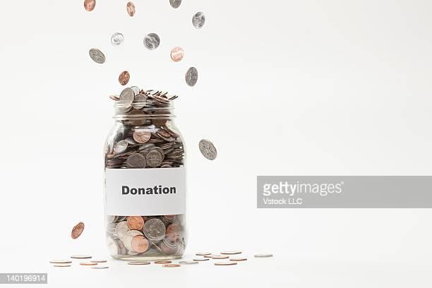 Studio shot of jar full of coins