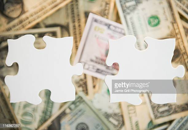 studio shot of jigsaw pieces against heap of money - things that go together stock pictures, royalty-free photos & images