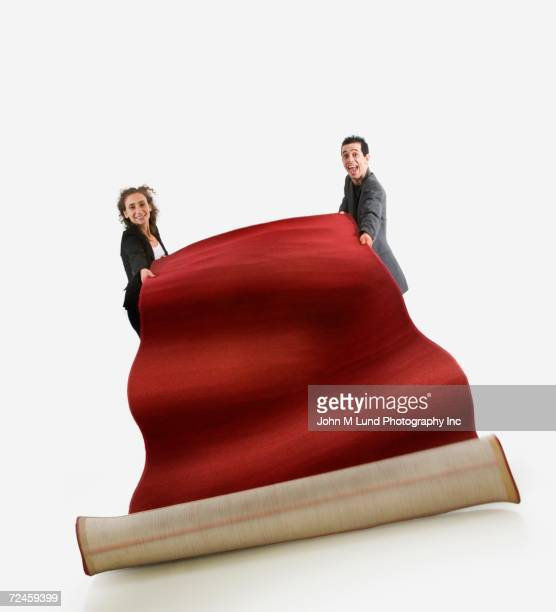 Studio shot of man and woman unrolling red carpet